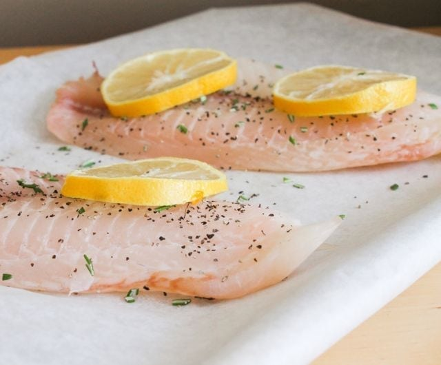 raw tilapia with lemon slices