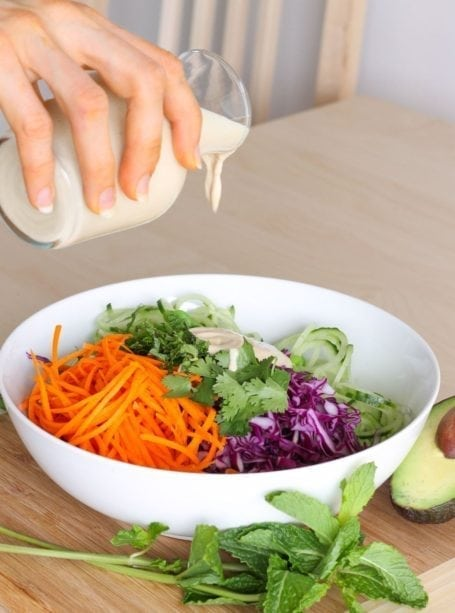 Pouring dressing on Edamame and Cucumber Noodle Salad