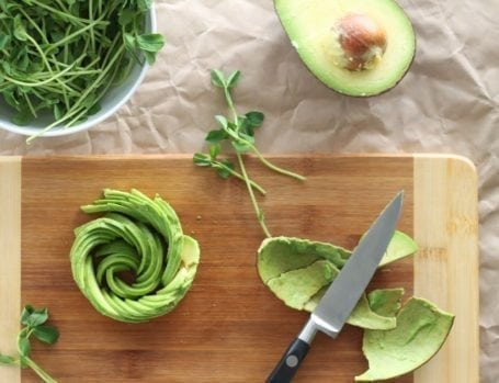 avocado flower on cutting board with knife and peel