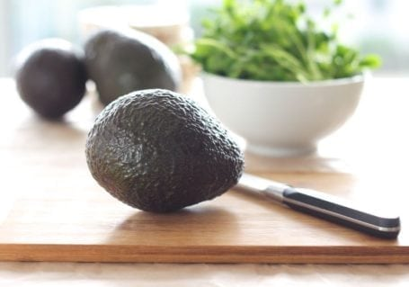 avocado on cutting board with a knife
