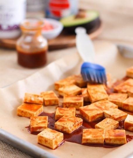 basting tofu in spicy sriracha marinade