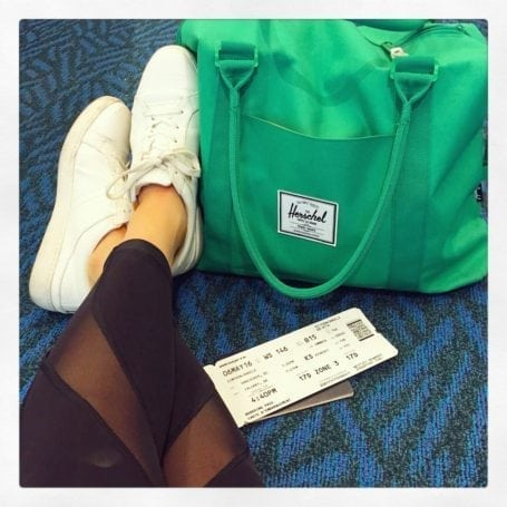 plane ticket and herschel bag at the airport