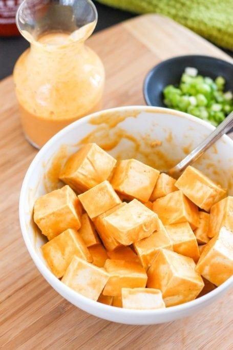 drizzling peanut sauce on tofu
