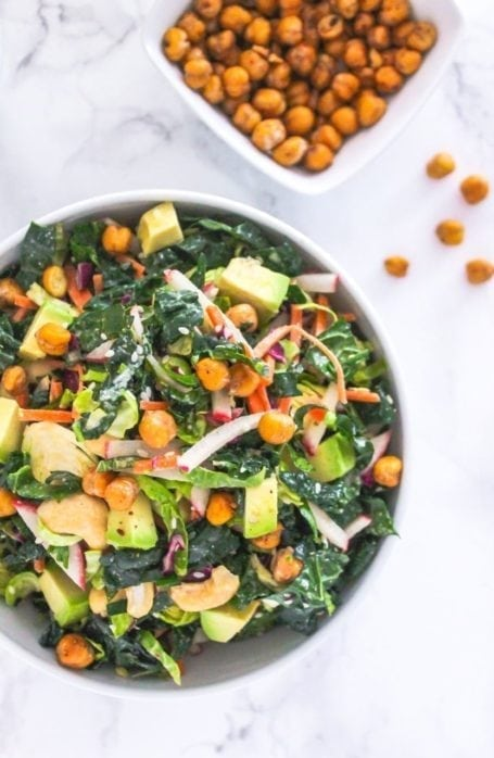 Lemon Tahini Kale Slaw with Crispy Chickpeas - Loaded with crunchy kale, radish, carrots, apple, avocado, cashews and seeds, this salad is bursting with nutritional goodies! via Eat Spin Run Repeat