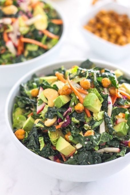 Lemon Tahini Kale Slaw with Crispy Chickpeas - Loaded with crunchy kale, radish, carrots, apple, avocado, cashews and seeds, this salad is bursting with nutritional goodies! Eat Spin Run Repeat