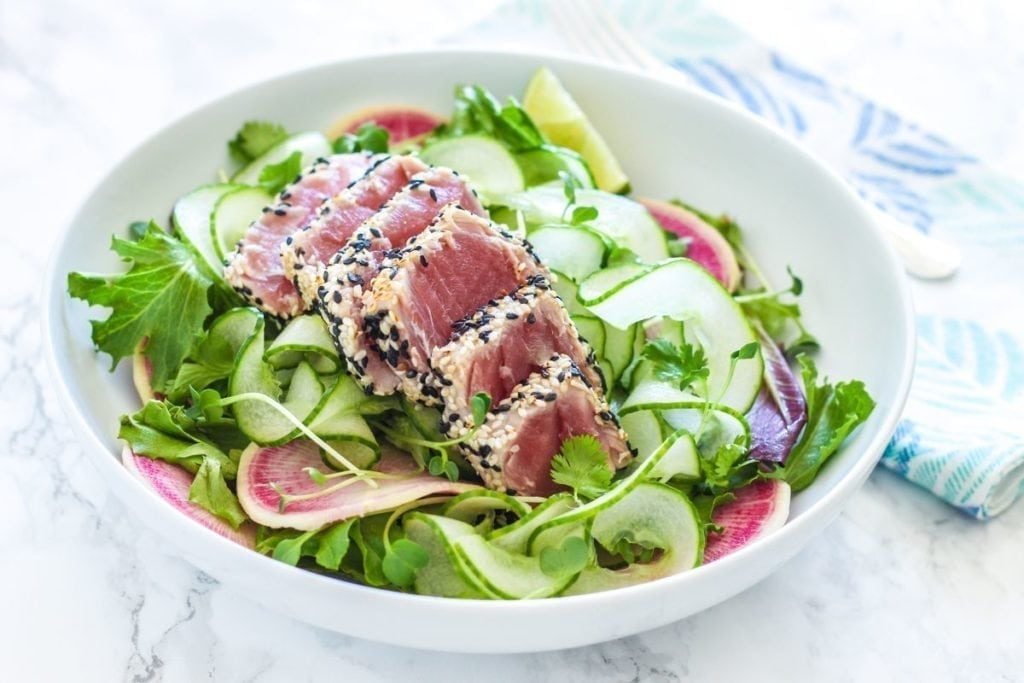 Sesame Crusted Ahi Tuna Salad - A quick and easy paleo-friendly salad loaded with bright produce and topped with crisp, seared-to-perfection ahi tuna. Full recipe via Eat Spin Run Repeat // @eatspinrunrpt